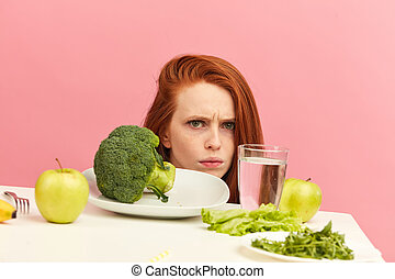 Frowning woman dislikes vegetables on table with disgusting...