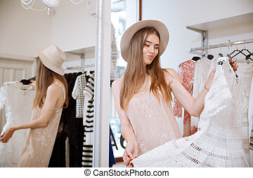 Frowning woman doing shopping and choosing dress in clothing store
