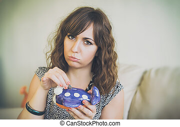 Frowning Woman Putting Coin in Airplane Bank