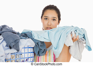 Frowning woman taking out dirty laundry - Frowning young...