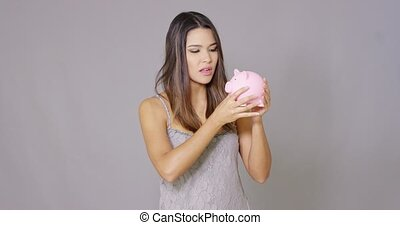 Frowning woman with fist and holding piggy bank against a...
