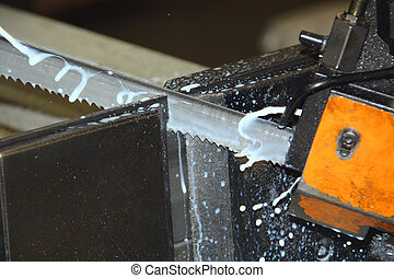 Frozen action shot of bandsaw blade showing teeth and coolant