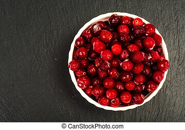 Frozen berries of cranberries in white bowl on black stone