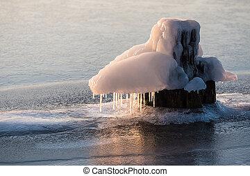Frozen bollard on a river in winter