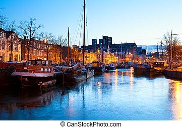 frozen canal with ships in Groningen in dusk, Netherlands