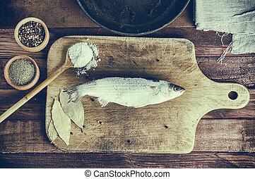 Frozen fish on the kitchen board