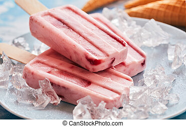 Frozen fruit popsicles with fresh strawberry chilling on a plate of crushed ice for a refreshing summer treat or snack