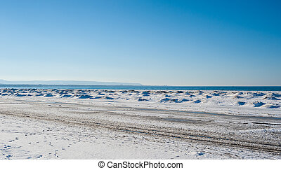 Frozen ice and sand dunes on beach in winter.
