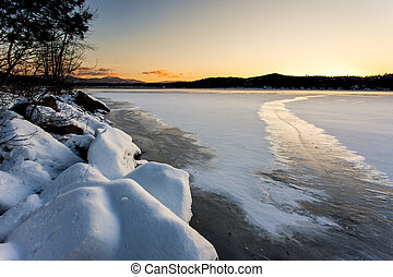 The snow covered rocky shoreline of Hauser Lake in Idaho at sunset.