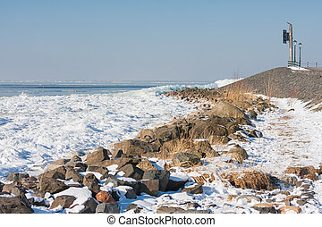 Frozen lake covered with stack of ice near breakwater