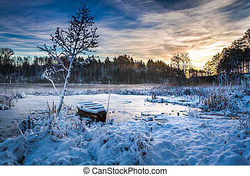 Frozen lake in winter at sunrise