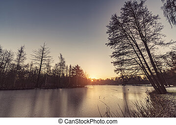 Frozen lake with tree silhouttes on the shore