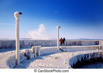 frozen lighthouse and pier on stormy winter day