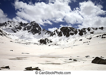 Frozen mountain lake covered with snow at sun day