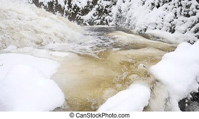 Frozen mountain stream. Snowy and icy stones in chilly water. Icicle bellow waterfall, stony and snowy stream bank with fallen branches. Close focus
