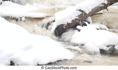Frozen mountain stream. Snowy and icy stones in chilly...