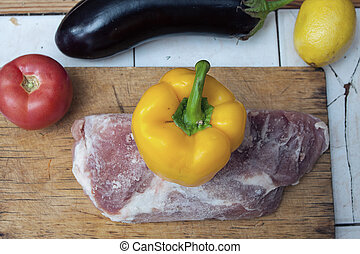 Frozen piece of meat on a wooden cutting board and yellow bell pepper, red tomato and eggplant on the table.