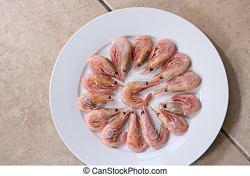 Frozen pink small shrimp prawns lobster on a white plate. Delicious food appetizer, seafood sea food defrosted