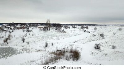 Frozen pond covered with a snow and plants covered with a snow near a village. Winter landscape