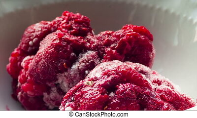 Frozen Raspberries Melting in a Plate on a White Background. Time Lapse