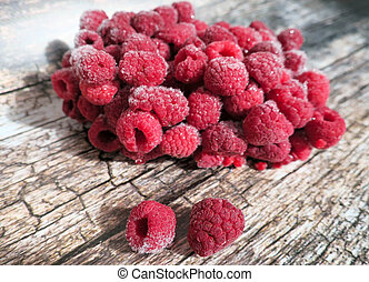 Frozen raspberries on wooden background