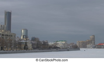 Frozen river and modern city. Empty square and floor with sky. Panorama