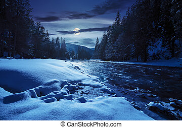 frozen river in forest at night - frozen river among conifer...