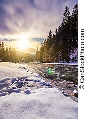 frozen river in forest at sunset - frozen river among...
