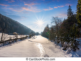 frozen river in forested mountains. beautiful scenery with...