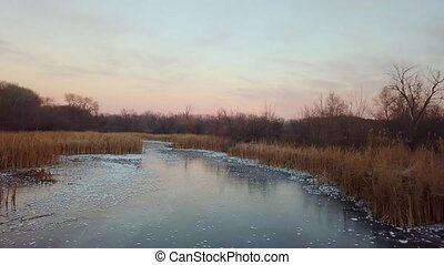 Frozen river with the purple, red and pink colors reflections of a fall sunset.