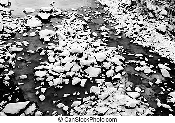 Frozen riverbed with snowy rocks in winter
