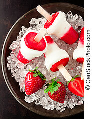 Frozen strawberry yogurt popsicles on crushed ice