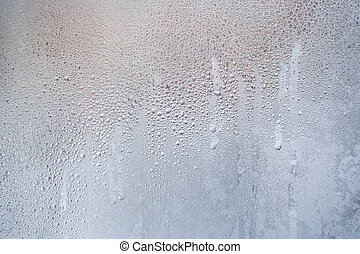 Frozen trickles and water drops on the winter window as background.