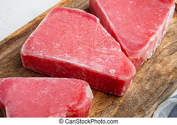 Frozen tuna fish steaks, on wooden tray, on white stone background