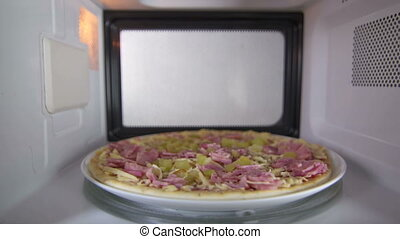 Frozen uncooked ham pizza defrosting in the microwave oven...