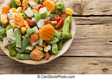 Frozen vegetables. - Frozen vegetables  in a wooden table.