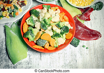 Frozen vegetables in plate and bowl