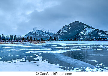 Frozen Vermillion Lake in Banff National Park with Mt. Rundle in the background. A cold, overcast morning just before sunrise.