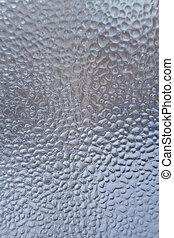 Frozen water drops on the winter window as background.