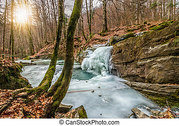 frozen waterfall abow the huge boulder in empty forest -...