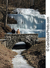 Frozen Waterfall - Frozen waterfall with couple on stone...