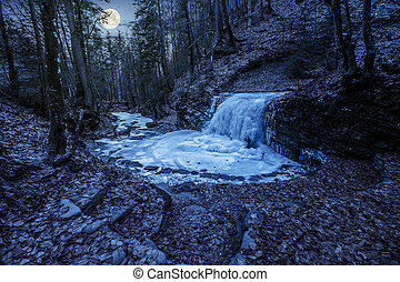 frozen waterfall in forest at night - frozen waterfall on...