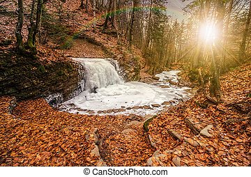 frozen waterfall in forest at sunset - frozen waterfall on...