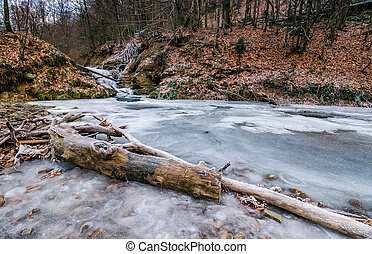 frozen waterfall in forest - frozen waterfall on the river...