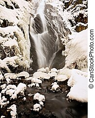 Frozen waterfall. Winter creek, icy stones and branches
