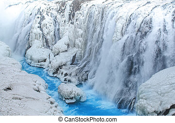 Frozen waterfall with clea blue water at early spring, Gullfoss, Iceland