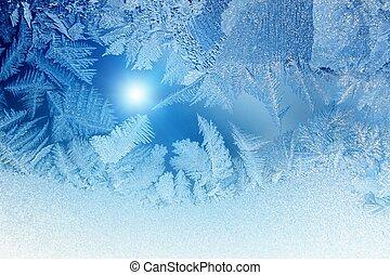 Abstract winter background - blue frozen window glass looks like fir-trees, bright sun.