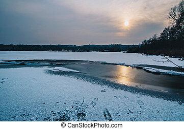 frozen winter lake at sunset