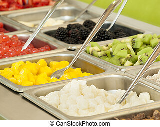 ?Frozen yogurt toppings bar. Yogurt toppings ranging from fresh fruits, nuts, fresh-cut candies, syrups and sprinkles.