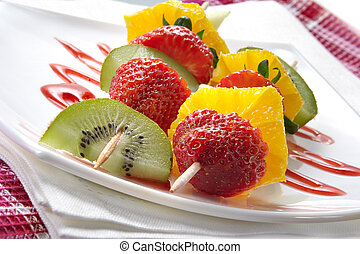 Fruit allsorts on skewers served atop of a plate decorated...